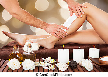 Male Beautician Waxing Woman's Leg In Spa - Cropped image of...