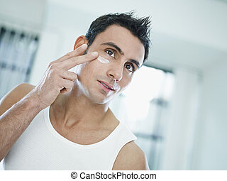 male beauty - young caucasian man applying eye cream on face...