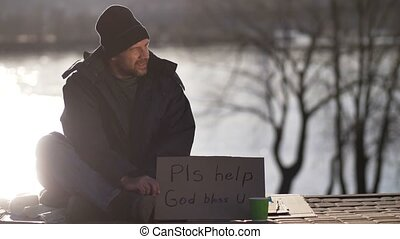 Male begging for money with cardboard sign - Mature male...