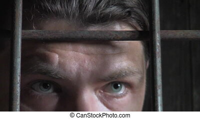 male behind bars, angry, eye closeup