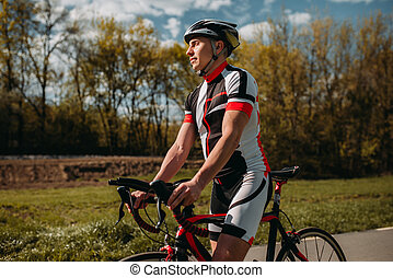 Male bicyclist in helmet and sportswear on bicycle