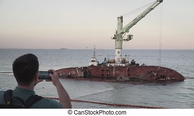Male blogger is broadcasting live on social networks on journey near sunken tanker Delfi near Odessa. Black Sea coast. Man creating video blog content using smartphone camera about ship accident.