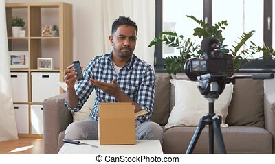 male blogger taking smartphone out of parcel box - mail...