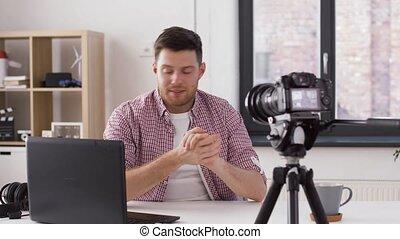 male blogger with camera videoblogging at home - blogging,...