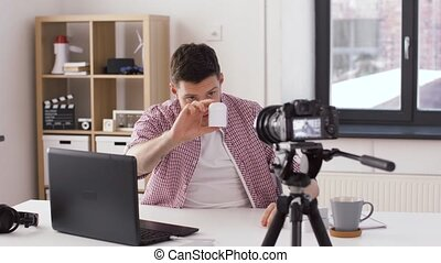 male blogger with earphones videoblogging at home -...