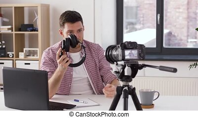 male blogger with headphones videoblogging at home -...