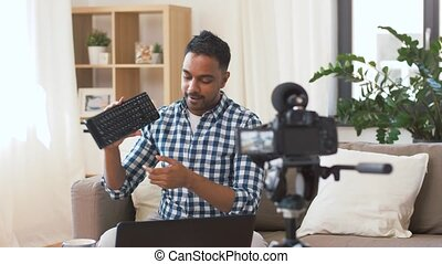male blogger with keyboard videoblogging at home - blogging,...