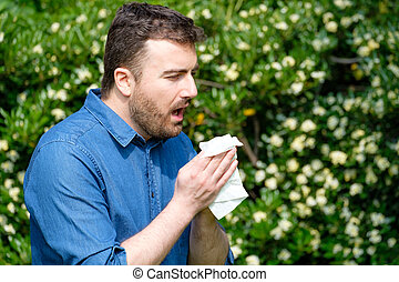 Male blowing his nose outdoors, having problem with allergy