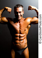 male bodybuilder posing on black