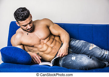 Male bodybuilder reading book on sofa - Handsome shirtless...