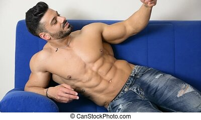 Male bodybuilder taking selfie photo on sofa - Handsome...