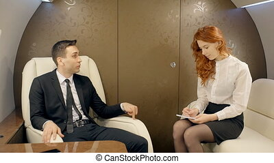 Male boss giving instructions to his female secretary in luxury jet.