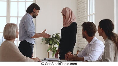 Caucasian male boss handshake promote praise successful female asian muslim worker wear hijab get good feedback applause at meeting, gender equality, employee recognition and office reward concept