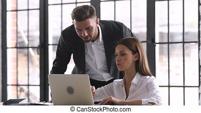 Male boss mentor helping female employee with online assignment teach intern in office, businessman executive supervisor helping businesswoman coworker with laptop at workplace check work progress