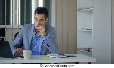 Male boss is taking coffee break sitting at workplace continuing working.