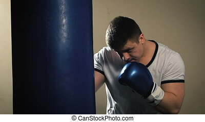 Male boxer at the gym hitting the punching ball. Closeup