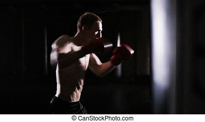 male boxer punches the punching bag in boxing gym - male...