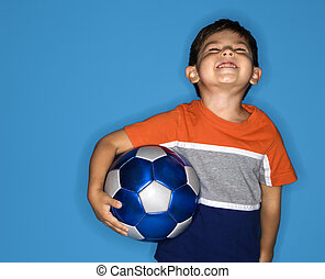 Male boy holding soccer ball.