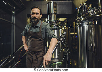 Male brewery worker in apron standing and looking at camera