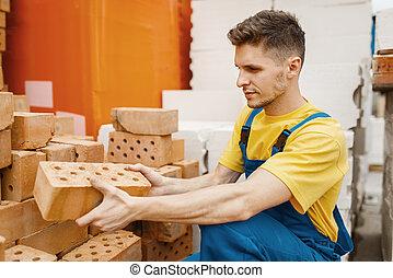 Male builder choosing bricks in hardware store