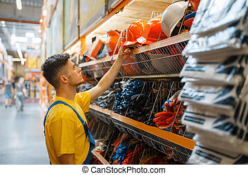 Male builder choosing helmet in hardware store - Male ...