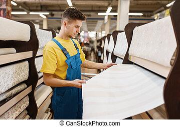 Male builder choosing wallpapers in hardware store