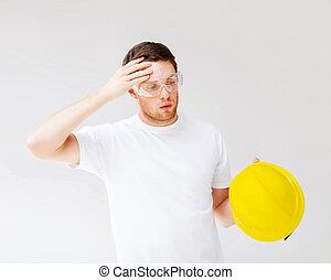 male builder in safety glasses taking off helmet - building,...