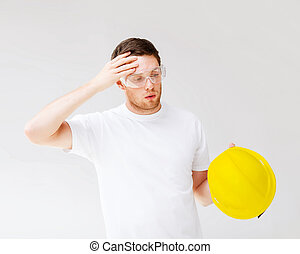 male builder in safety glasses taking off helmet - building,...
