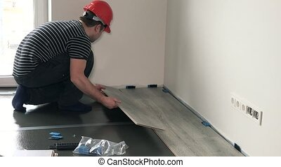 Male builder laminate flooring in new flat house. Static...