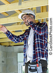 male builder on the phone