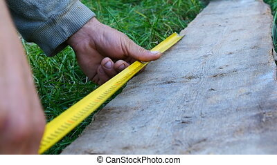 Male builder taking measurements of wooden board with a measuring tape or yardstick