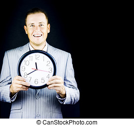 Male business person in gray suit holding a clock