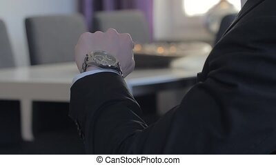 Male businessman looks at his watch to tell the time