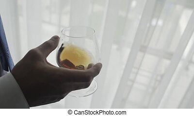 Male businessman with a glass of whiskey by the window.