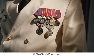 Male captain wearing jacket with medals is posing and standing at modern interior. Closeup view of male professional dressed in white suit poses for camera and stands in light interior. One millennial persona shows formal uniforms adorned with orders and awards during work hours. Concept: human, ...