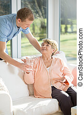 Male care assistant caring about elder woman