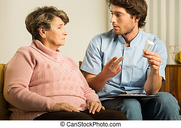 Male caregiver supporting old woman