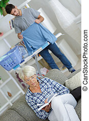 male caregiver working behind couch with senior reading a...