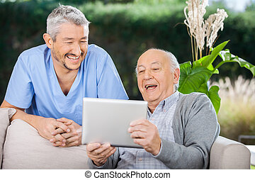 Cheerful male caretaker and senior man using tablet PC at nursing home porch