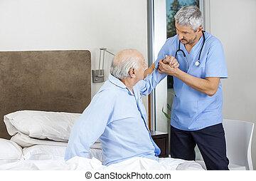 Male Caretaker Assisting Senior Man
