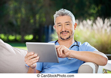 Portrait of male caretaker using tablet computer while sitting at nursing home porch