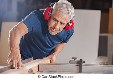 Concentrated senior male carpenter cutting wood with tablesaw in workshop