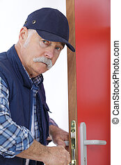 male carpenter fixing lock in door