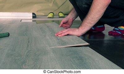 Male carpenter hands install wooden board on floor. Handheld...