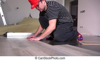Male carpenter lay wooden laminate boards on floor in new house room