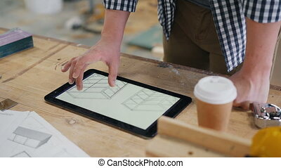 Male carpenter looking at technical drawings of furniture on tablet screen