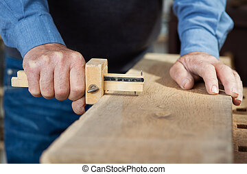Male Carpenter Measuring Wood In Workshop