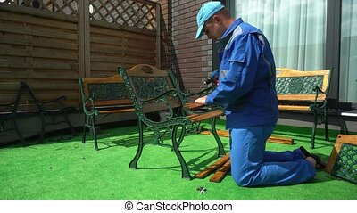 Male carpenter screw chair with electric screwdriver. Worker...