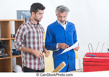 male carpenter showing something to coworker