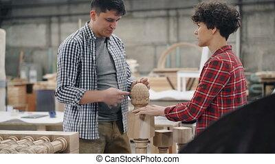 Male carpenter talking to female apprentice in workshop...